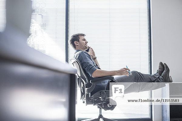 Geschäftsmann im Büro am Telefon mit erhobenen Füßen