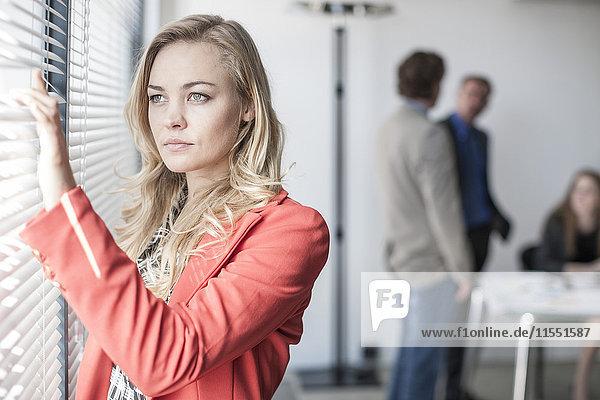 Geschäftsfrau mit Blick aus dem Bürofenster und Menschen im Hintergrund
