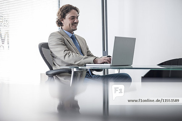 Lächelnder Geschäftsmann am Schreibtisch mit Laptop