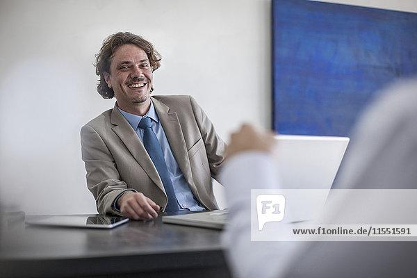 Lächelnder Geschäftsmann am Schreibtisch mit Laptop und Blick auf den Mann