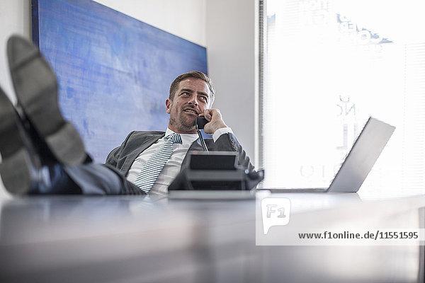 Geschäftsmann am Schreibtisch mit erhobenen Füßen beim Telefonieren