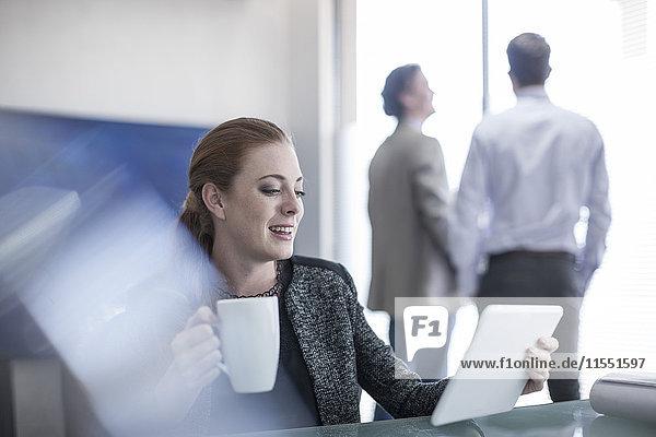 Lächelnde Frau im Büro mit einer Tasse Kaffee und einem digitalen Tablett