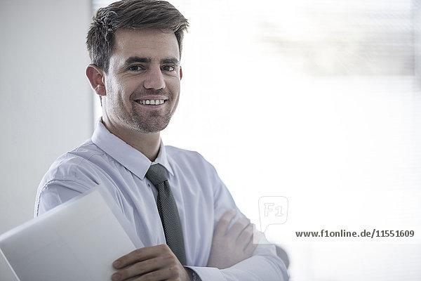 Porträt eines lächelnden Geschäftsmannes mit Papieren