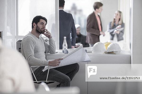 Mann sitzt im Büro und denkt über einen Bauplan mit Schutzhelmen nach.