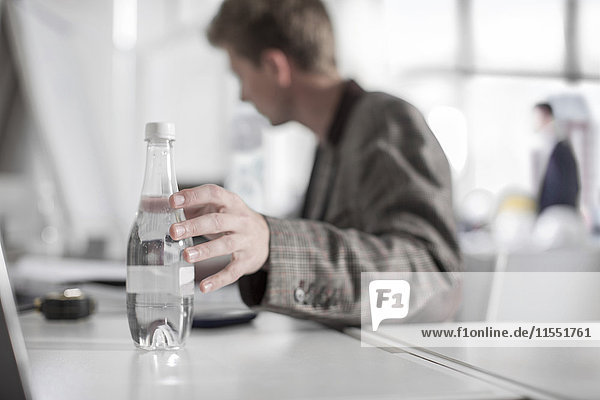 Mann im Büro am Schreibtisch greift nach Wasserflasche