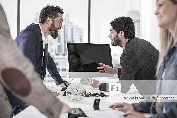 Zwei Männer reden an der Rezeption.