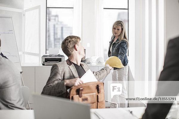 Frau übergibt Schutzhelm an Amtskollegin