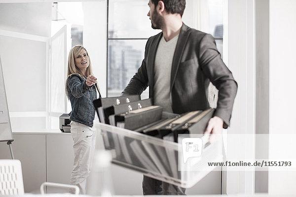 Mann im Büro  der eine Kiste mit Akten trägt  die mit einer Frau spricht.