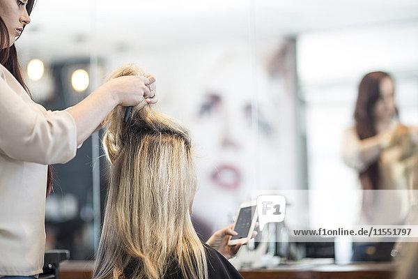 Friseur im Friseursalon prüft die Haare des Kunden