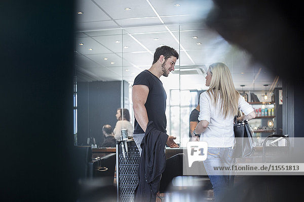 Frau im Friseursalon im Gespräch mit dem Friseur