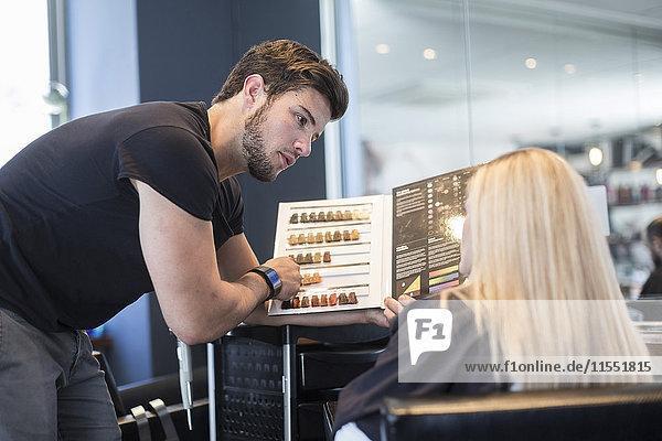 Frau im Friseursalon bei der Wahl der Haarfarbe