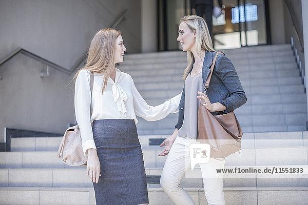 Zwei junge Geschäftsfrauen im Gespräch auf der Treppe