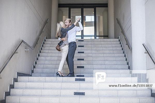 Geschäftsfrau und Mann tanzen auf der Treppe