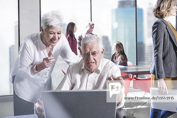 Ältere Kollegen im Büro und Besprechung im Hintergrund