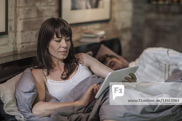 Frau mit Tablette im Bett mit einem Mann  der neben ihr schläft.