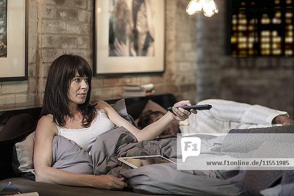 Frau  die im Bett fernsieht  mit einem Mann  der neben ihr schläft.