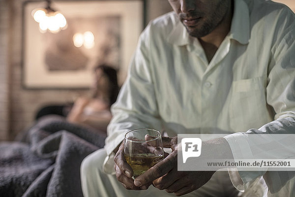 Mann auf dem Bett sitzend bei einem Drink