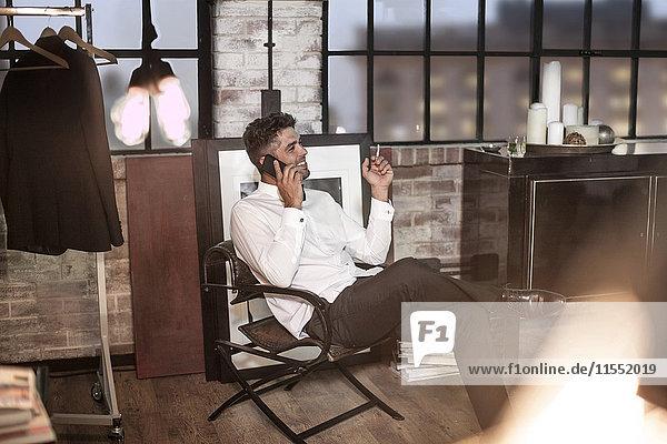 Entspannter Mann in einer Wohnung  der telefoniert und eine Zigarette raucht.
