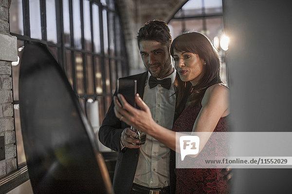 Paar in eleganter Kleidung mit einem Selfie