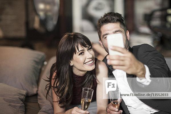 Lächelndes Paar in eleganter Kleidung trinkt Champagner im Bett und nimmt einen Selfie.