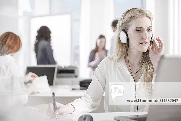 Porträt der Frau am Schreibtisch im Büro mit Kopfhörer