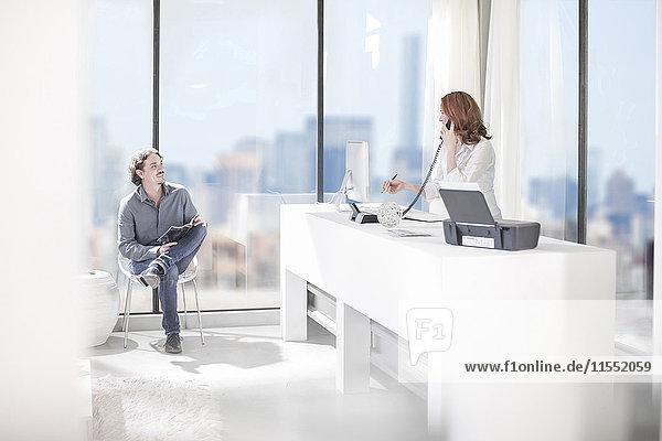 Sekretärin am Telefon und Mann auf dem Stuhl