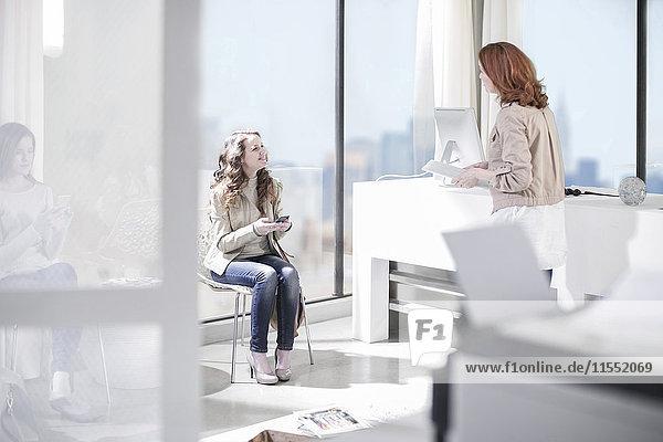 Zwei Frauen sprechen in der Bürolobby