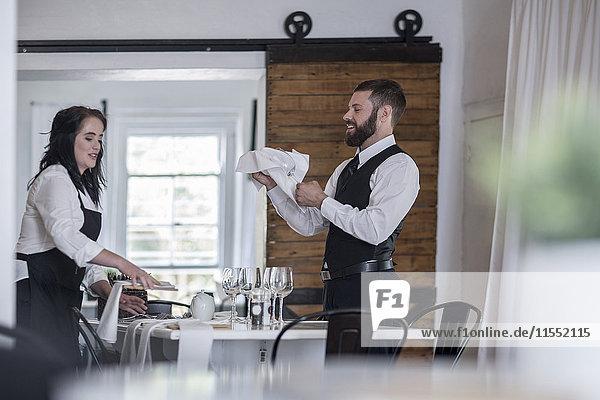 Kellnerin und Kellnerin Polieren von Weingläsern und Besteck im Restaurant