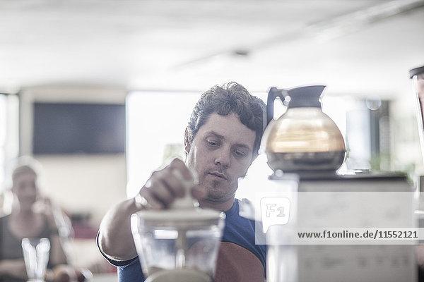 Mann  der im Coffee-Shop arbeitet und Kaffee zubereitet.