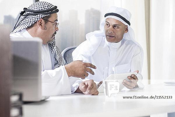 Zwei Geschäftsleute aus dem Nahen Osten sitzen im Büro und schauen sich das digitale Tablett an.