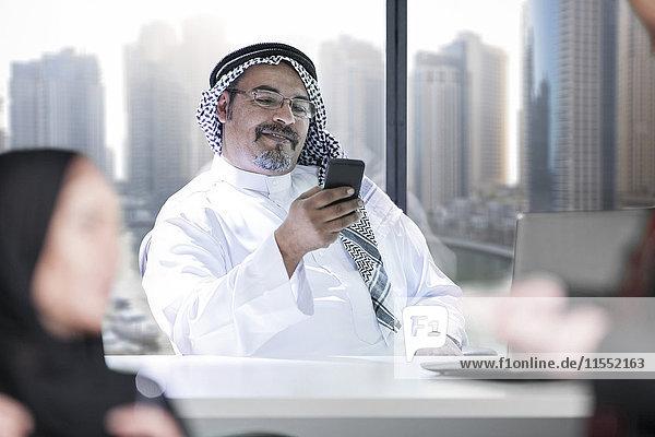 Nahost-Geschäftsmann im Büro mit Smartphone