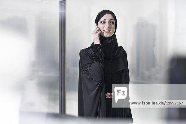 Junge Geschäftsfrau aus dem Nahen Osten im Büro am Telefon