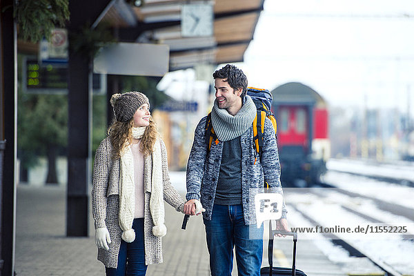 Smiling young couple on station platform