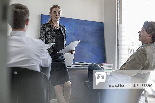 Geschäftsfrau im Büro bei der Übergabe von Dokumenten an Kollegen