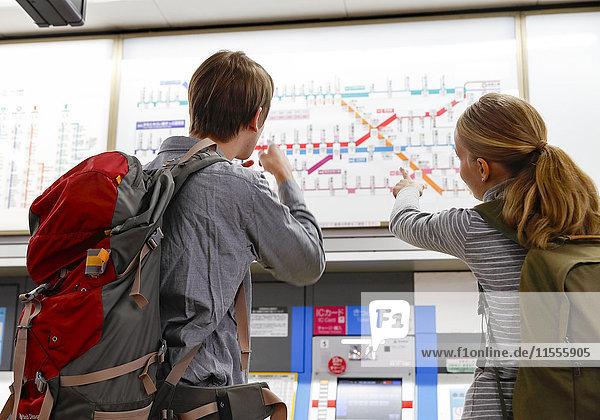Caucasian tourist couple at train station  Tokyo  Japan