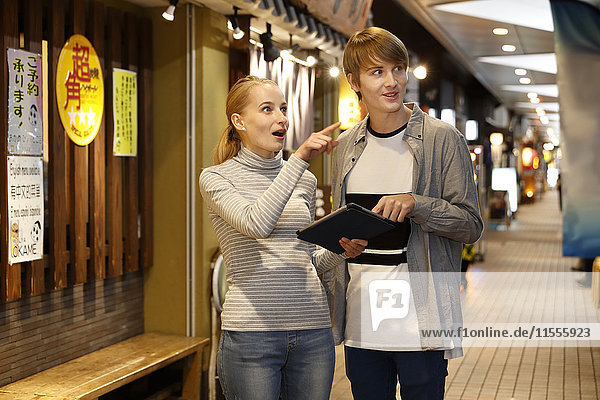 Caucasian tourist couple looking for a restaurant at a traditional shopping street  Tokyo  Japan