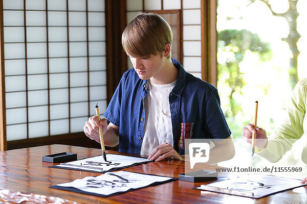 Caucasian man practicing calligraphy at traditional Japanese house