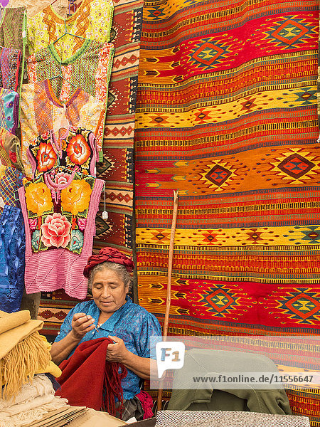 Woman sewing in market with background of handmade rugs  Oaxaca  Mexico  North America