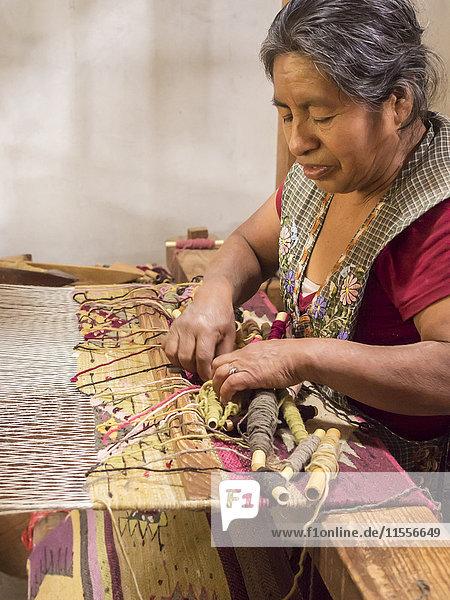 Zapotec woman weaving a rug on a floor loom in farmhouse  Teotitlan del Valle  Oaxaca  Mexico  North America