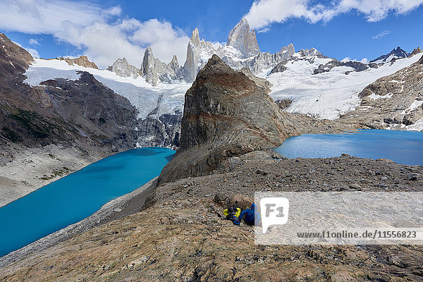 A couple in mountain gear rests on rocks with view to Lago de los Tres and Mount Fitz Roy  Patagonia  Argentina  South America