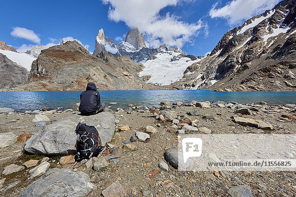 A lone figure in mountain gear rests on rocks with view to Lago de los Tres and Mount Fitz Roy  their backpack on the ground  Patagonia  Argentina  South America