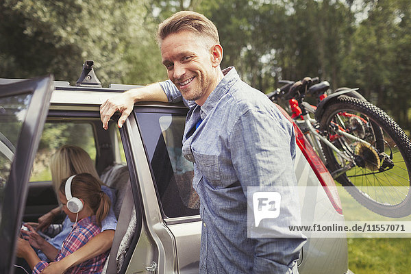 Portrait smiling father leaning on car with mountain bikes