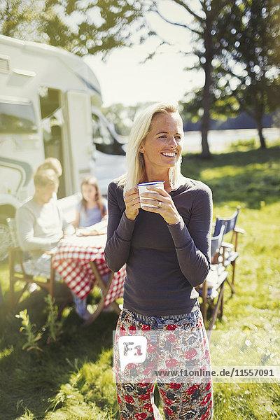 Lächelnde Frau im Pyjama trinkt Kaffee vor dem sonnigen Wohnmobil
