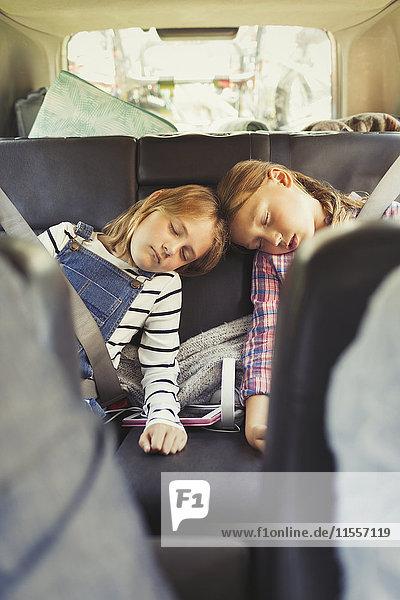 Müde Schwestern schlafen auf dem Rücksitz des Autos