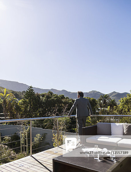 Pensive businessman on sunny balcony patio  looking at mountain view