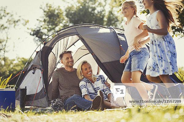 Eltern beobachten glückliche Töchter  die im sonnigen Zelt des Campingplatzes herumlaufen.