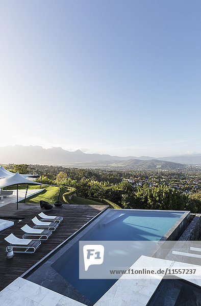 Home showcase exterior infinity pool and patio with mountain view under sunny blue sky