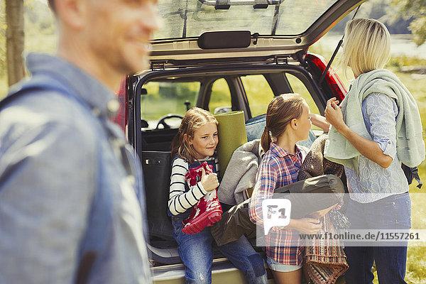 Familie beim Entladen der Campingausrüstung aus dem Auto