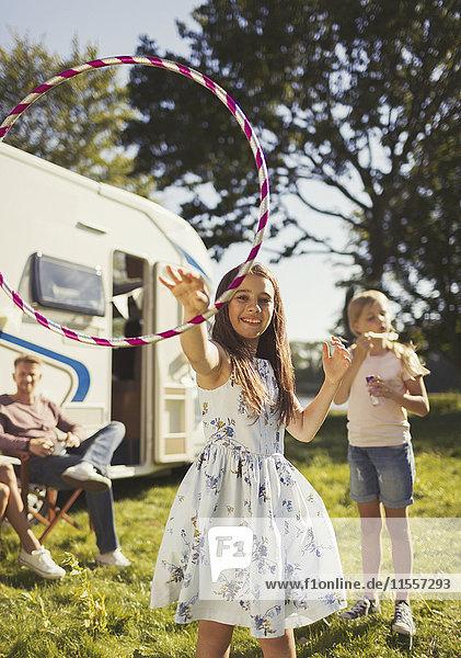 Portrait Verspieltes Mädchen beim Spinnen von Plastikreifen vor dem sonnigen Wohnmobil