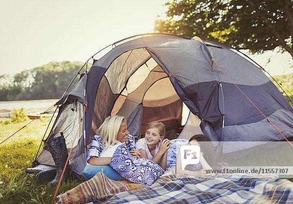 Mutter und Töchter reden und entspannen im Zelt auf dem Campingplatz